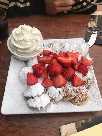 Poffertjes with butter, icing sugar, freshly whipped cream and strawberries