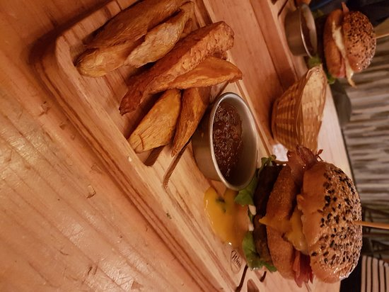 Hamburguesa con medallon de carne, medallon de muzza rebozado y frito, panceta crujiente y huevo, viene con cebollas caramelizadas, alioli y podes elegir batatas o papas fritas.