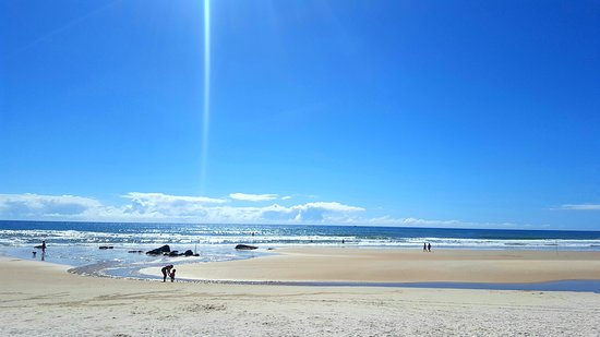 Praia em frente ao resort, com água morna, ondas pequenas e areia branca.