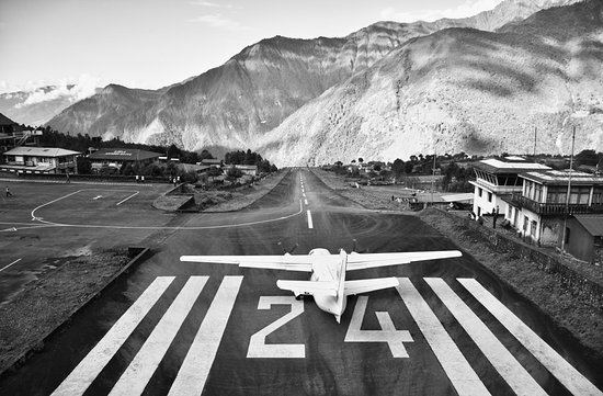 "A small plane departing the ""World's Most Dangerous Airport"" (Tenzig-Hillary Airport) in Lukla after dropping off new adventurers hoping to reach Everest Base Camp.  The airport runway is only 1,724ft /527m long with a 12% uphill pitch - a cliff on one side and a fenced stone wall on the other.  This airport serves as the gateway for travelers looking to explore the Himalayans and hopefully lay their eyes upon the tallest mountain in the world - Mount Everest (aka Sagarmatha or Chomolungma)."