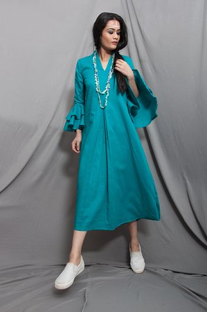 Нью-Дели, Индия: Long cowl dress radiates a sixties boho-luxe vibe with its fluid fit and bell sleeves. It can be worn with heels for an evening occasion or dressed down with a simple pair of sandals for daytime.