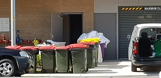 couldn't park inside for two night s as carpark floor was being painted, photo shows laundry outside, staff folding and sorting laundry outside of rollerdoor.