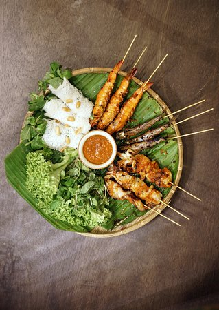 Mekong Special - Grilled spicy seafood platter. Three servings of tiger prawns, squid, and capelin. Served with fresh vegetables, mint leaves wrapped with fine rice vermicelli, and home-made spicy sauce. $28.80++