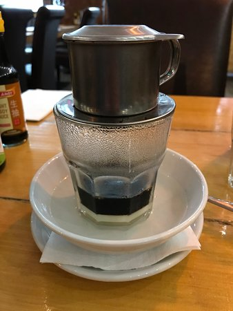 Vietnamese coffee (slowly dripping from the container above into the the glass with warmed and sugared condensed milk)