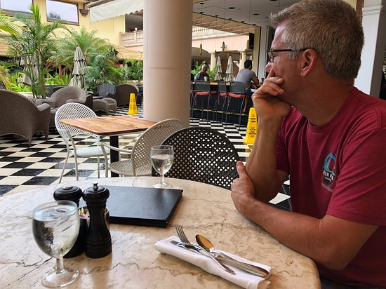 Longhi's Wailea: My husband tanned and ready for breakfast. Outside under the umbrellas. Nice view of plants but that's it but it's still a nice atmosphere.