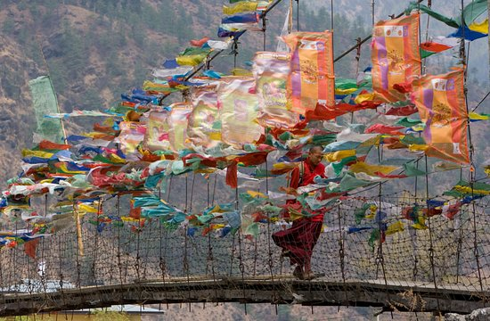 Bumthang, Bhutan: Monk walking on suspension bridge with fluttering prayer flags.This one is from one of our Bhutan photography tours.