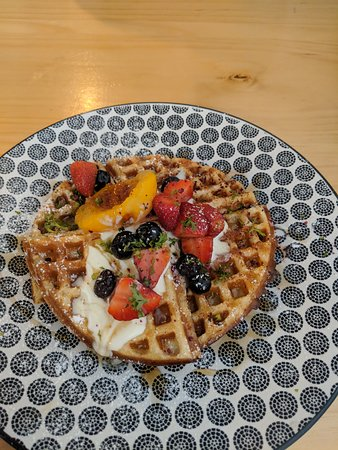 Delicious waffles with fruit, candied peach and berries