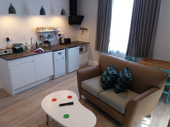 Five Valleys Aparthotel : A typical living room with kitchenette, sofa and dining table