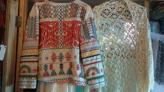 embroidered jacket with tribal design from gujarat and small pearls to the left and ahandknitted gypsy open poncho.