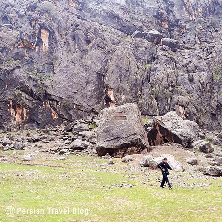 """Khong-e Azhdar Rock Relief This rock relief which also is known as Khong-e Nowruzi has two opposite relief faces, is located in a village, called Khong-e Azhdar 15 kilomtere north of Izeh in Khuzestan province. The relief is faced to the village, dated back to """"Old Elamite"""" depicts a procession in which a king is seated on a throne and seven Elamite figures are standing to his right. Above the scene is a rectangular panel having no figure or inscription."""