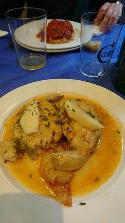 Merluza a la sidra y al fondo el plato de bacalao