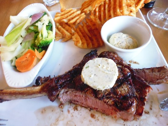 Rustlers Steakhouse and Grill: Rib Eye steak with cross-cut chips, vegetables, and blue cheese butter -- cooked medium