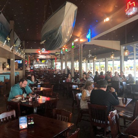 San Leon, TX: Main dining area - note longboat hung from ceiling, window wall toward bay to right, pelican pier behind the camera.  Objects along panel to left are salt-water spinning rods in brackets.  Lots of neon beer logos!