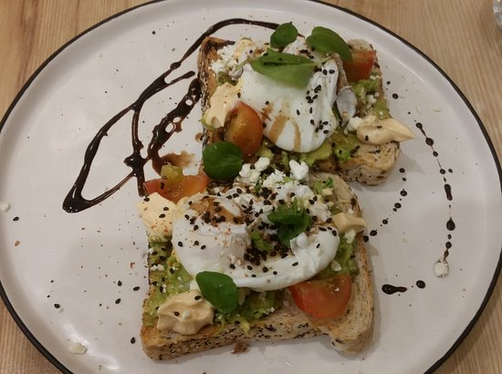 The Alkaline Cafe: Poached eggs and avocado on toast. I suppose the extra cost is for the artistic squirt of balsamic syrup