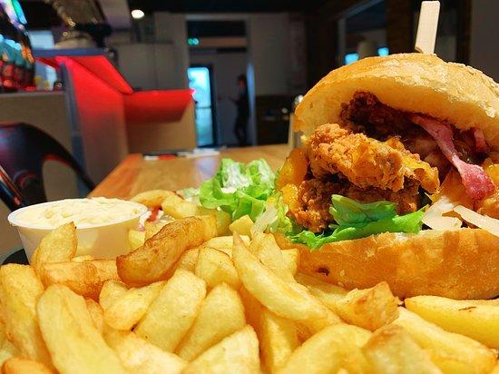 """Le Peplum: L'hamburger """"Jupiter"""" : des filets de poulet français marinés et panés maison, du bacon croustillant, du cheddar fondu et la sauce barbecue Heinz qui relève légèrement le tout."""