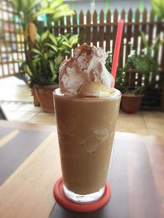 coffee blended with vanilla ice cream and top with whipped cream, ice cream and with sprinkle of cinnamon powder