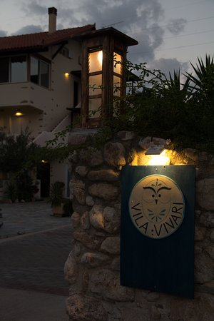Vivari, Greece: Romantic sunset view of a lighted wooden exterior lamp glowing warm yellow light at the hotel entrance with the hotel sign standing out against the stone wall under a yellow warm light. In the background is the hotel front with lighted exterior lamps glowing warm light