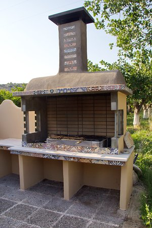 Detail of the grill for the guests at Vila Vivari showing precise hand made grill suitable for anything up to a lamb. The grill is decorated by a country style ceramic embroidery. In the background showing pistachio and orange orchards.