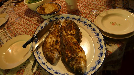 Three different size fish grilled at the Vila Vivari being served on a village style plate with bread and serving next to it. Table is covered by a country style flower table cloth.