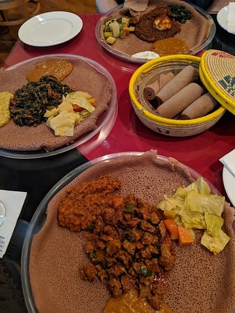 Queen of Sheba: yummy lunch! On the bottom clockwise is Tibse, zuresh, doro wot. It is eaten with injera-sourdough bread without utensils.