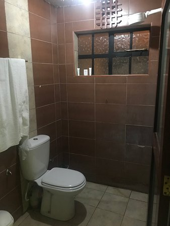 Kiserian, Kenya: Note shower is over the toilet for single rooms, white head in top right, it is the electric heating unit.