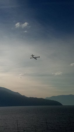 Il promontorio dell'Abbazia di Piona visto dalla sponda opposta del Lago di Como, con aerei Canadair in sorvolo