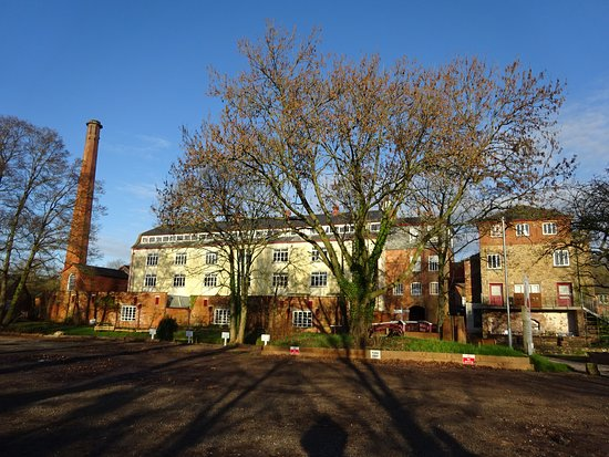 Uffculme, UK: Standing in the car park, the steam engines by the chimney, the looms in the central building and the large water wheel to the right of the main building. The cafe is in the right building