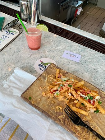 Jamaican me crazy fries with a frozen concoction next to the pool