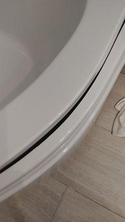 Dirty towel on floor. Broken tub.