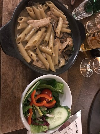 Main course from festive menu. Chicken pasta with salad