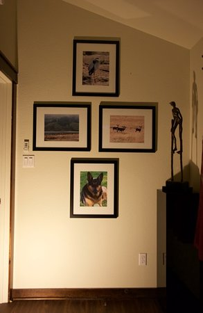 """Wall displaying four J. Foster photographs in a 16 x 20"""" framed 4C print format and the bronze sculpture Zancos by Victor Salmones the internationally acclaimed sculptor."""
