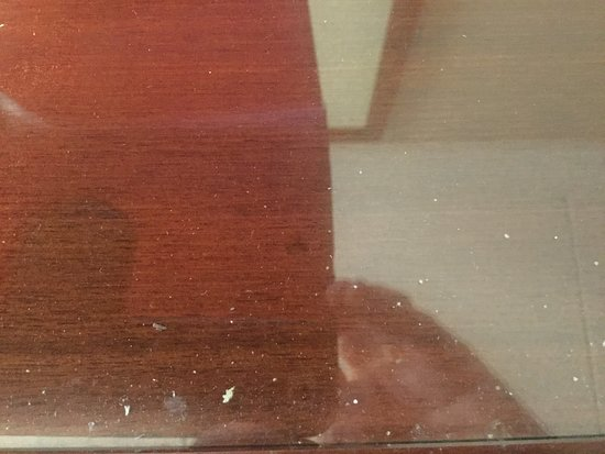 DoubleTree DFW Airport North: Fluff and debris under the glass panel on the guestroom desk