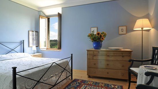 """""""Camera Azzurra"""": natural wood floors and double bed, with whitewashed walls painted in sky-blue, the typical colour of bedrooms in the traditional local farmhouses..."""