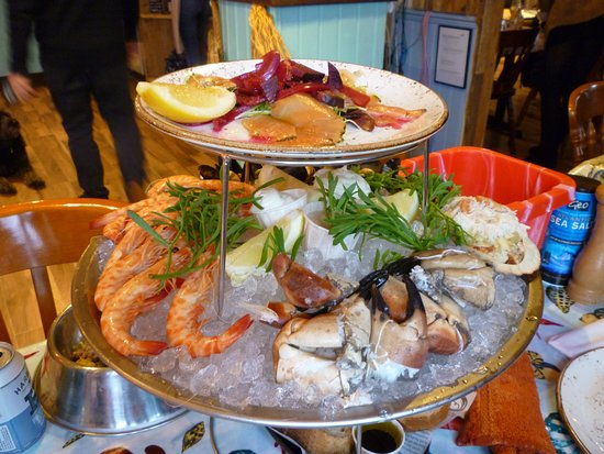 Bigbury, UK: A selection of shell-on prawns, mussels, dressed crab with lemon wedges and marie rose, mayonnaise and garlic mayonnaise all served on a bed of ice and garnished with samphire.
