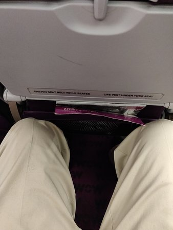 """WOW air [no longer operating]: This is what WOW calls  the """"""""""""Big Seat"""""""""""" on the flight from YYZ to KEF.  I am pulling my knees back as far as I can and they touch teh (not reclined) seat in front.  This worsened my knees condition for the all my stay in Iceland."""