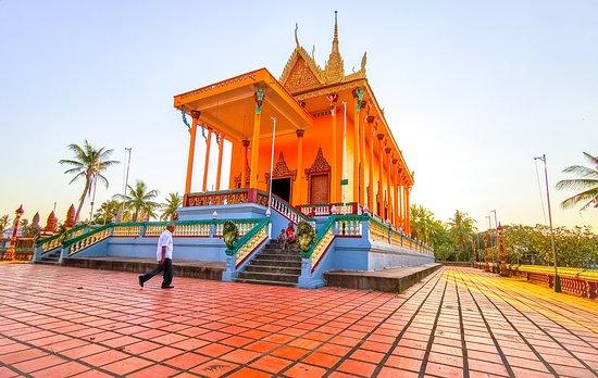 Sun sets over the already yellow pagoda in Skun, Phnom Penh region in Cambodia, making the scene into a range of yellow, orange and gold.