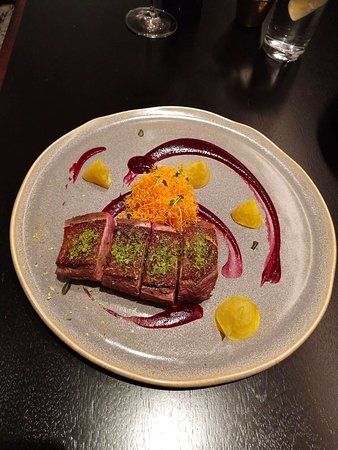 Greater London, UK: Roasted free range duck breast with crunchy sweet potatoes, beetroot red fruits purée and pistachios