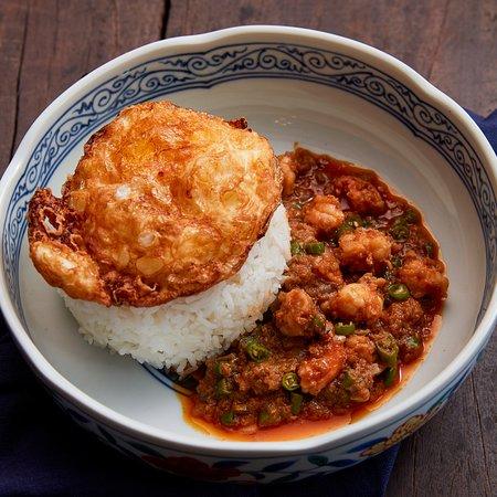 Stir-Fried Prawn Fat & Bird Chilli on Rice with Crispy Fried Egg ข้าวราดมันกุ้งผัดพริกขี้หนู  Many different kinds of prawn fat stir-fried with bird chilli until bubbling, served on rice with deep fried egg. มันกุ้งจากทุกสถาบันที่มารวมตัวกันจนเป็นซอสมันกุ้งสูตรลับ ผัดกับพริกขี้หนูสวนราดบนข้าวสวยร้อนๆ ทานคู่กับไข่ดาวกรอบฟู 240-