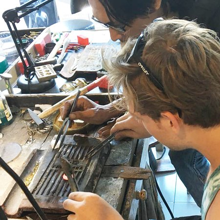 One of our 1/2 day silversmithing students making his own pendant design with the assistance of on of our expert metalsmiths, Jono.