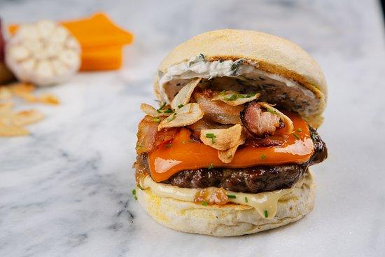 Cheddar Passion - Clássico Hambúrguer de carnes nobres, pão branco, queijo cheddar, molho LGB, bacon, cebola roxa refogada na laranja, lâminas de alho crocante, molho Cervelle de Canut com ricota e pasta de alho assado