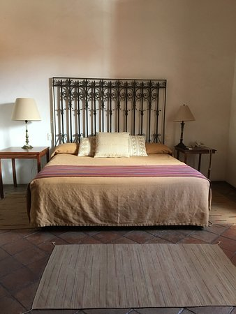 Bedroom closest to entry: lovely hand wrought iron bed with hand woven linens in nuetral hues