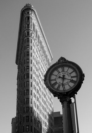 Black and white photograph of the NYC Flatiron Building with the Fifth Avenue Building clock. Matted prints available in various sizes at the gallery.