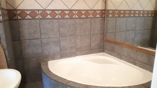 Blue Sea Unit 4, The en-suite full bathroom is modern, tiled floor to ceiling, with a big romantic corner bath, big shower, toilet and hand basin. Towels and soap is provided please bring your own beach towels