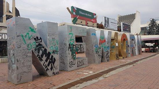 Pristina, Kosovo: Symbolizujący uzyskaną w 2008 roku niepodległość kraju, niestety zaniedbany, popisany flamastrami i sprayami, w tle kiczowate billboardy. Nie jest utrzymany w takim stanie, jak być powinien.