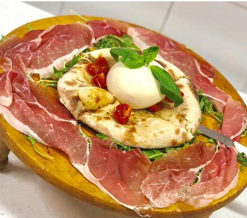 Burrata pugliese con cappello di basilico adagiata su cacciannanz contornata da crudo di Parma e pachino
