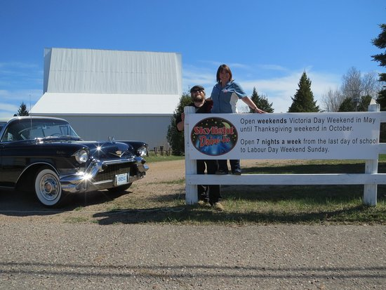 Pembroke, Kanada: Owners Kathy and Kevin Marshall posing with their 1957 Cadillac outside the front gate to the Drive-In!