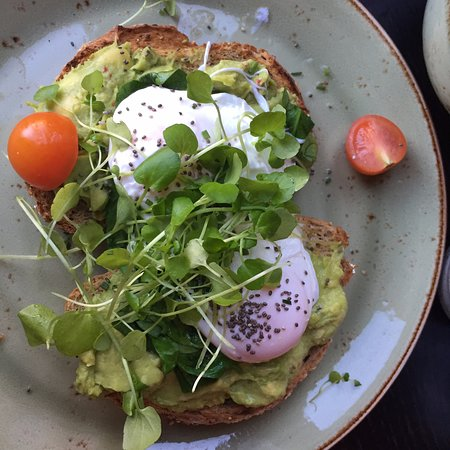Lunch Bread with avocado and poached egg, water cress, chia seeds and cherry tomatoes.