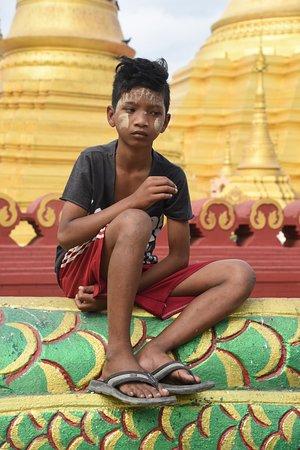 Myawadi, Myanmar: Ragazzo birmano di fronte allo Shwe Muay Wan , tempio dorato a Myawaddy, Stato Karen nel Myanmar.