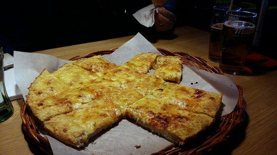 Sarebbe la focaccia al dubbio ed esageratissimo formaggio che loro chiamano Pizza Margherita