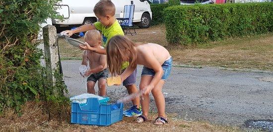 Laver la vaisselle au camping à Villedieu less Poêles est un plaisir pour les petits.